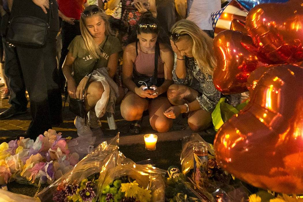 People visit a makeshift memorial for victims of the Route 91 Harvest mass shooting located on Las Vegas Boulevard and Reno Avenue in Las Vegas, Tuesday, Oct. 3, 2017. Richard Brian Las Vegas Revi ...