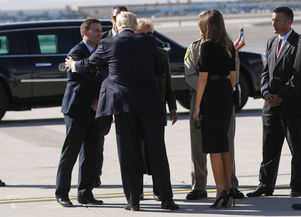 Nevada Attorney General Adam Laxalt, left, greets President Donald Trump, with First Lady Melania Trump, at McCarran International Airport in Las Vegas on Wednesday, Oct. 4, 2017. A gunman opened  ...