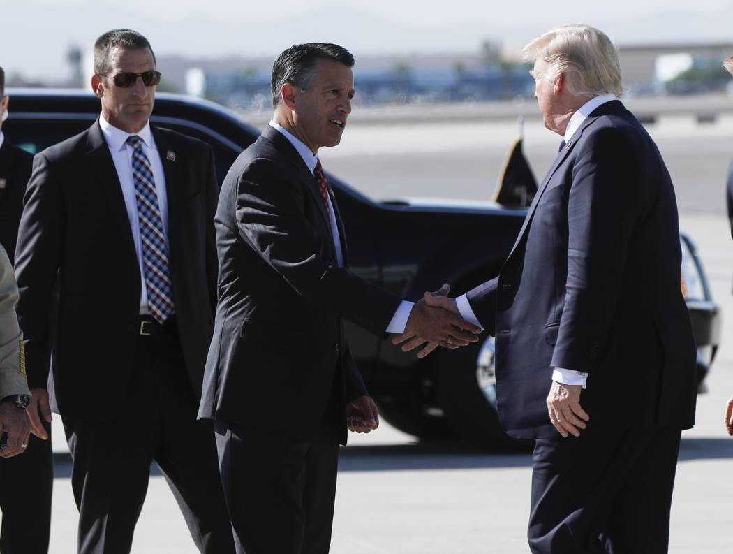Gov. Brian Sandoval, left, greets President Donald Trump upon his arrival at McCarran International Airport in Las Vegas on Wednesday, Oct. 4, 2017. A gunman opened fire on attendees of a music fe ...