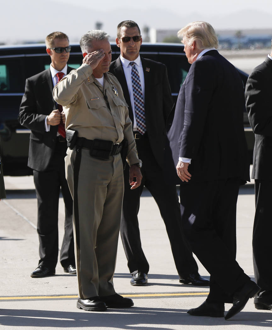 Clark County Sheriff Joe Lombardo, left, salutes as President Donald Trump arrives at McCarran International Airport in Las Vegas on Wednesday, Oct. 4, 2017. A gunman opened fire on attendees of a ...
