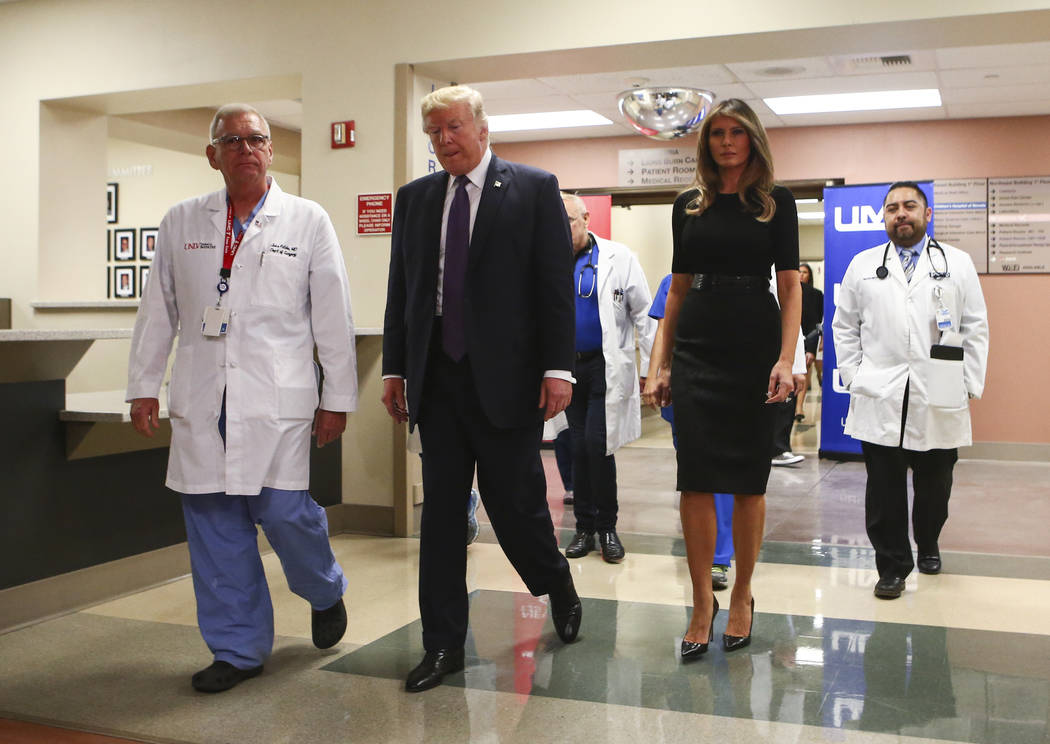 President Donald Trump and First Lady Melania Trump walk alongside physician John Fildes, left, after visiting victims at University Medical Center in Las Vegas on Wednesday, Oct. 4, 2017. A gunma ...