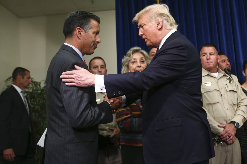 President Donald Trump embraces Nevada Gov. Brian Sandoval at Metropolitan Police Department headquarters in Las Vegas on Wednesday, Oct. 4, 2017. A gunman opened fire on attendees of a music fest ...