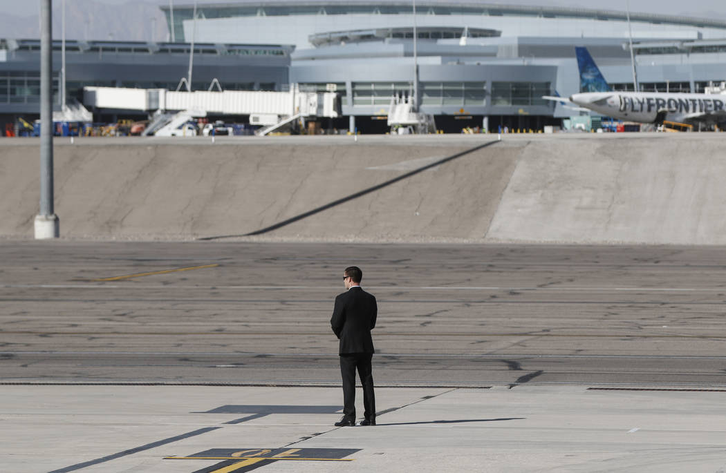 A Secret Service officer waits for the arrival of President Donald Trump at McCarran International Airport in Las Vegas on Wednesday, Oct. 4, 2017. A gunman opened fire on attendees of a music fes ...