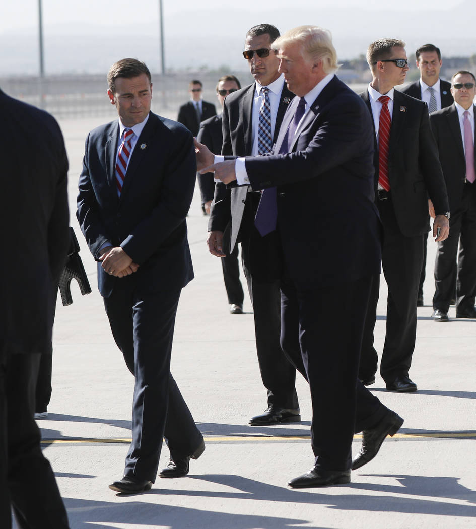 Nevada Attorney General Adam Laxalt, left, talks with President Donald Trump at McCarran International Airport in Las Vegas on Wednesday, Oct. 4, 2017. A gunman opened fire on attendees of a music ...