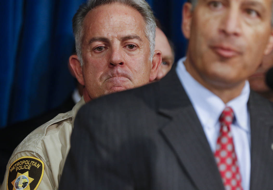 Clark County Sheriff Joe Lombardo, left, and listens as Gov. Brian Sandoval speaks at Metropolitan Police Department headquarters in Las Vegas on Wednesday, Oct. 4, 2017. A gunman opened fire on a ...