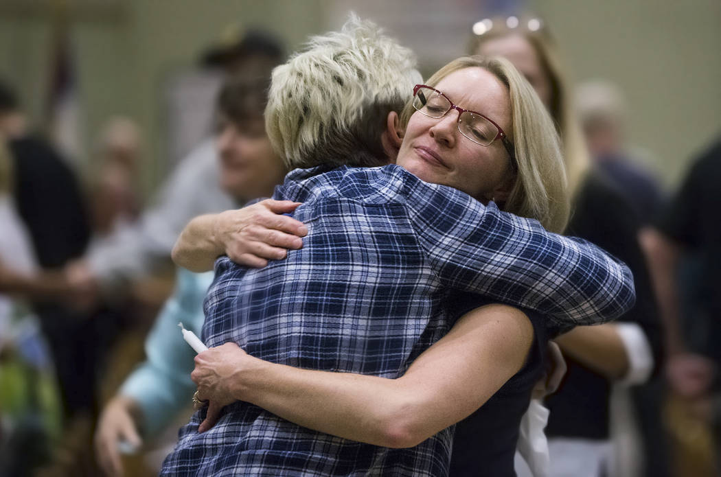 Catherine Daruwalla, front/middle, hugs Sarah Birch during a candlelight service in response to Sunday's Route 91 festival shooting on Tuesday, October 3, 2017, at Good Samaritan Lutheran Church,  ...