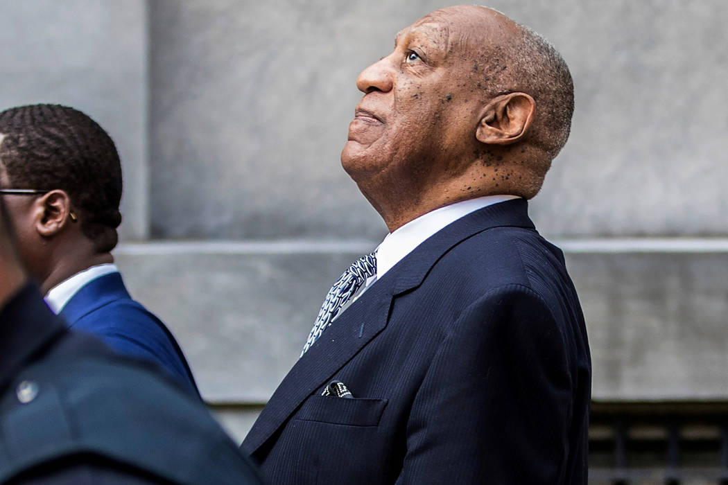 Bill Cosby leans back to listens to words of encouragement from onlookers  outside Montgomery County Courthouse