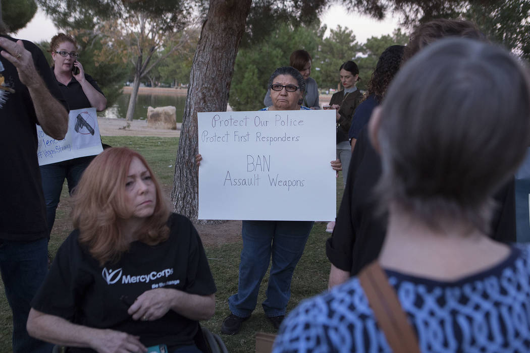 Attendee Maria Reyes holds a sign during a gathering at Sunset Park hosted by Women's March on Washington - Nevada in Las Vegas, Wednesday, Oct. 4, 2017. Attendees voiced their demands for stricte ...