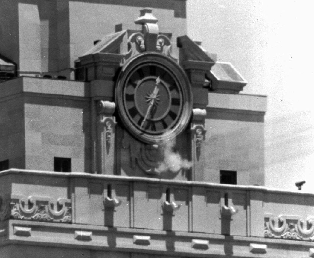 Smoke rises from the sniper's gun as he fired from the tower of the University of Texas administration building in Austin, Texas, on crowds below in 1966. (AP Photo/File)