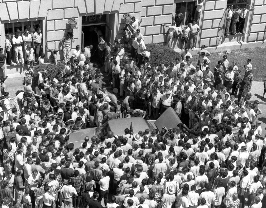 A crowd of curious people gather at the entrance to the Univ. of Texas tower in Austin, Texas on August 1, 1966, after the shooting spree by Charles J. Whitman was ended by police bullets. (AP Photo)