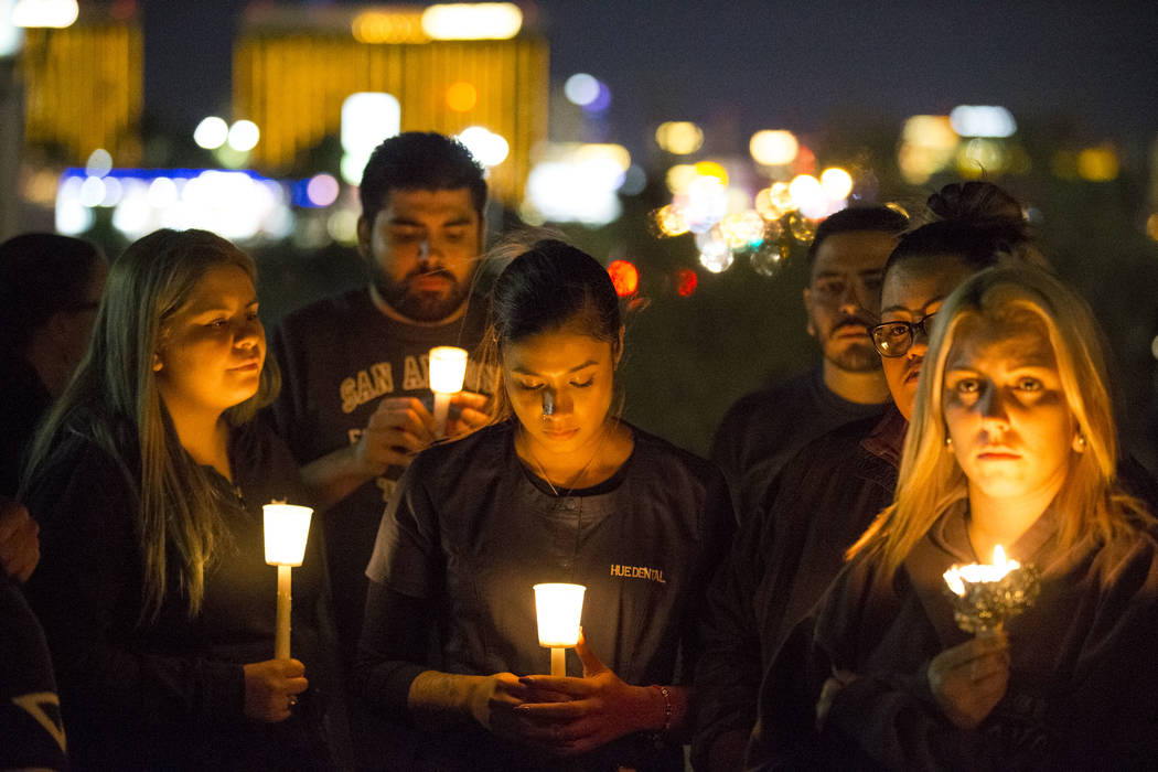 Participants take part in a candlelight vigil condemning the mass shooting at Route 91 Harvest country music festival on Monday, Oct. 2, 2017, at the intersection Las Vegas Boulevard South and Wes ...