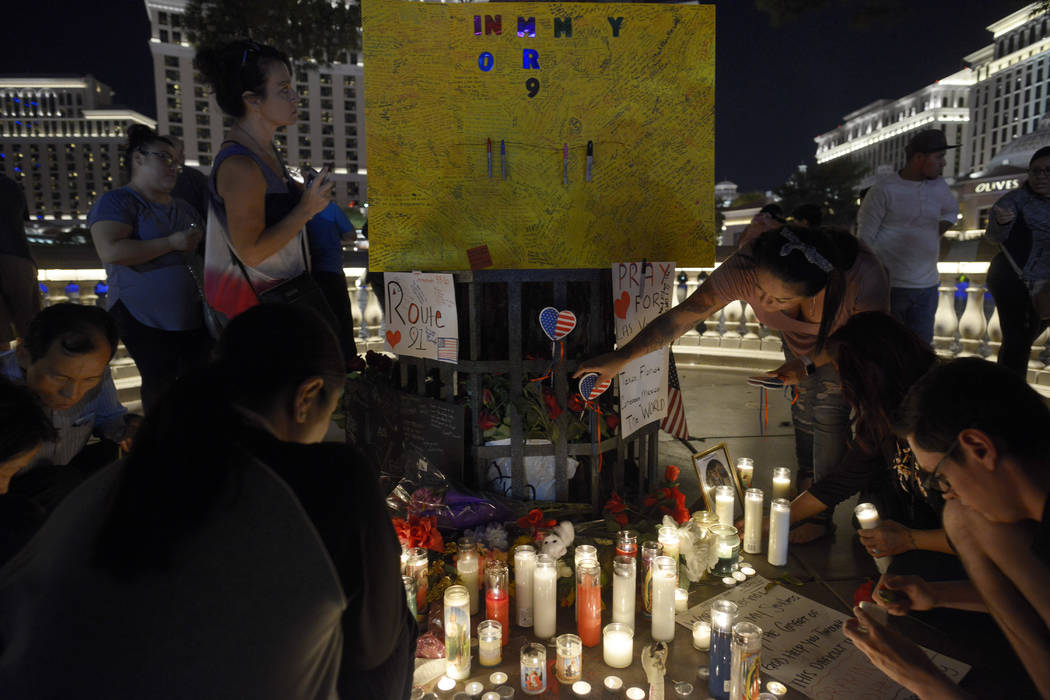 People light candles at an impromptu memorial in front of the Bellagio to pay their respect to the victims and first responders of the previous Sunday's mass shooting. (Sam Morris/Las Vegas News B ...