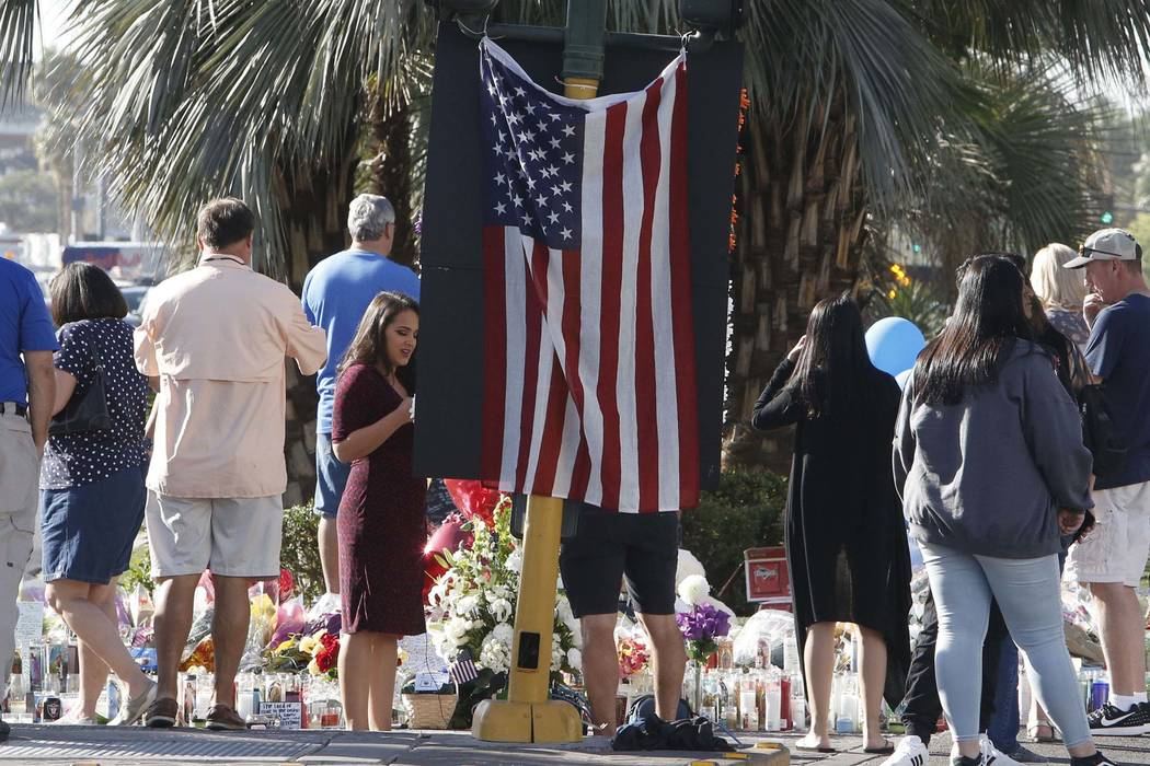 People gather to pay their respects to the victims of the Route 91 Harvest mass shooting at a makeshift memorial on Las Vegas Boulevard near Mandalay Bay on Thursday, Oct. 5, 2017, in Las Vegas. ( ...
