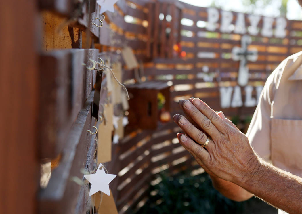 Volunteer Lyle Hoffman pays honor to the fallen victims of the Route 91 Harvest Festival shooting while he and other volunteers help plant a permanent memorial garden for the victims being planted ...