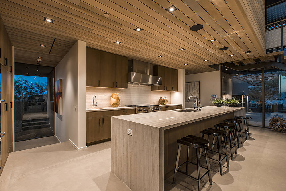 The kitchen's large island is topped with white-striped quartzite stone with a natural waterfall design. (Ascaya)