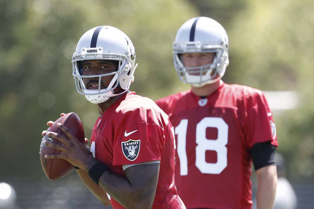 The Oakland Raiders back up quarterback Ej Manuel prepares to pass the ball as Connor Cook, right, looks on during teams practice at Raiders Napa Valley training complex in Napa., Calif., on Satur ...