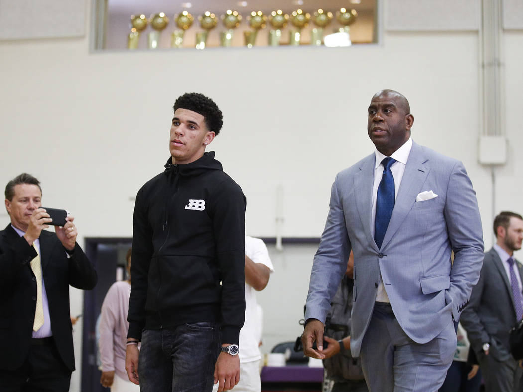 Los Angeles Lakers draft pick Lonzo Ball, left, and Magic Johnson arrive for a news conference, Friday, June 23, 2017, in El Segundo, Calif. (AP Photo/Jae C. Hong)