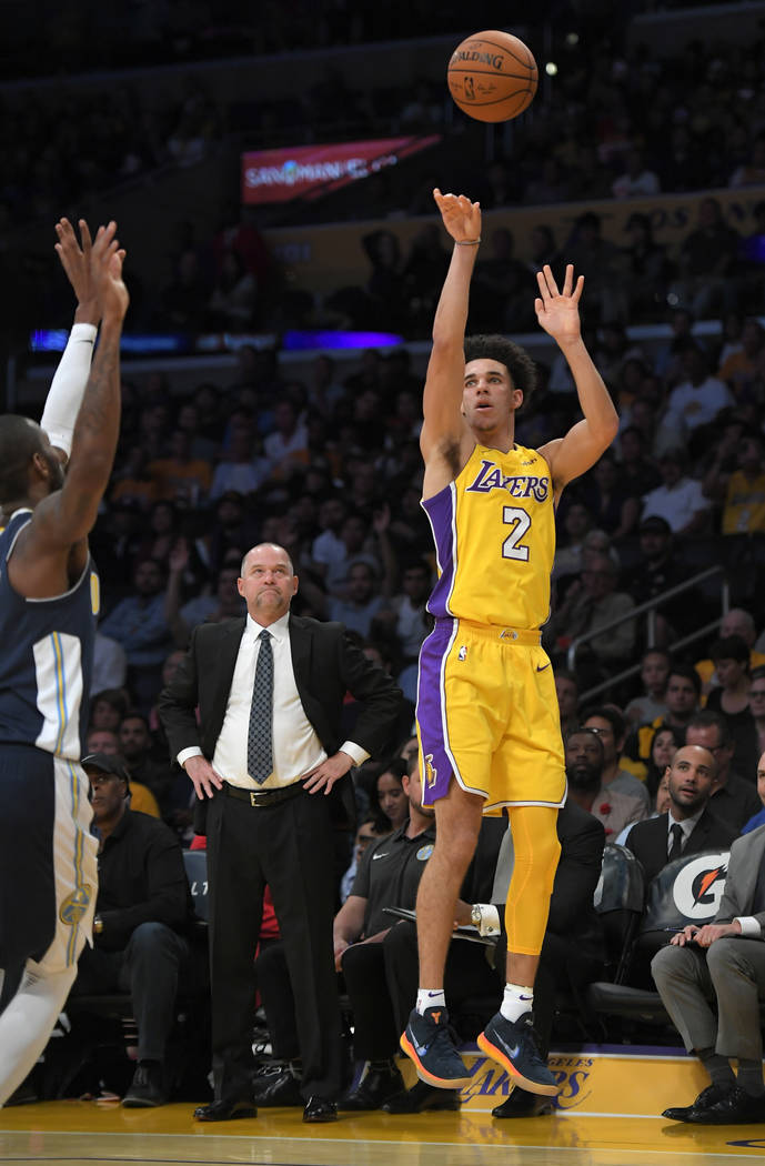 Los Angeles Lakers guard Lonzo Ball, right, shoots as Denver Nuggets guard Will Barton defends during the second half of a preseason NBA basketball game, Monday, Oct. 2, 2017, in Los Angeles. The  ...