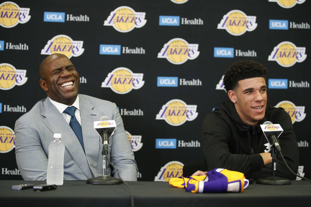 Magic Johnson, left, laughs as Los Angeles Lakers draft pick Lonzo Ball tells reporters he hadn't been born when Johnson played for the Lakers. during a news conference, Friday, June 23, 2017, in  ...