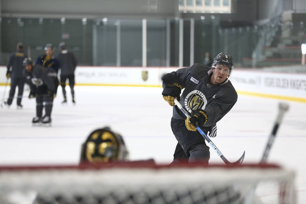 Vegas Golden Knights defenseman Griffin Reinhart (8) takes a shot on Knights goalie Marc-Andre Fleury (29) in a drill during the NHL team's practice at the City National Arena in Las Vegas, Wednes ...