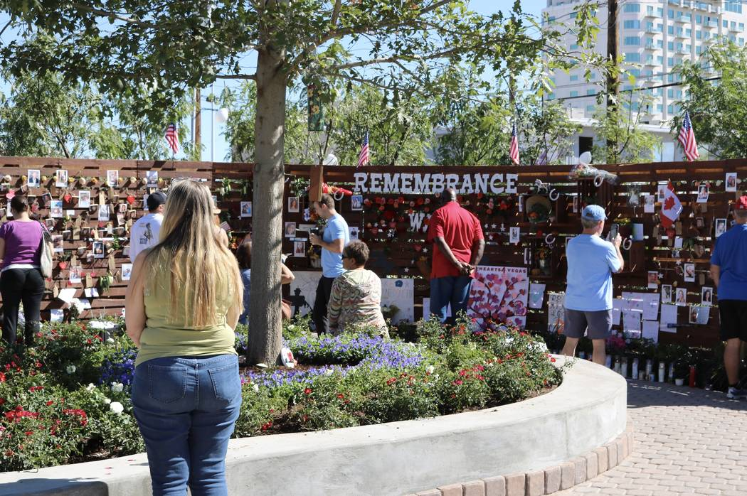 """Attendees walk past the """"Remembrance Wall"""" at the Community Healing Garden in Las Vegas, Saturday, Oct. 7, 2017. The city of Las Vegas dedicated the new healing garden to victims of Sunday's shoot ..."""