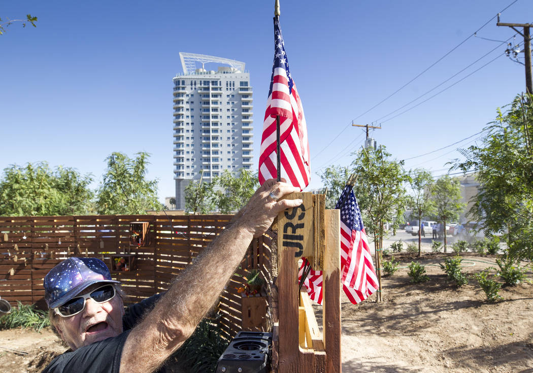 Las Vegas resident Michael James Smith, 66, puts a U.S. flag on the prayer wall as he volunteers at an under-construction community healing garden located at South Casino Center and East Charlesto ...