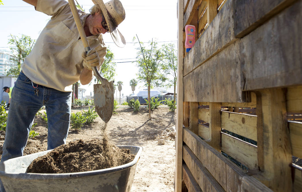 Las Vegas native and construction worker Lyle Hoffman, 58, shovels soil from a wheelbarrow as he volunteers at an under-construction community healing garden located at South Casino Center and Eas ...