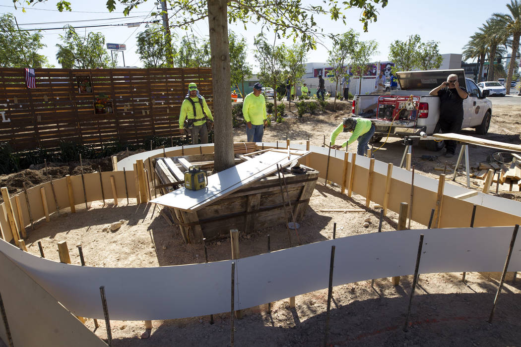 Landscapers work on a heart-shaped flower planter at an under-construction community healing garden located at South Casino Center and East Charleston boulevards in downtown Las Vegas, Thursday, O ...