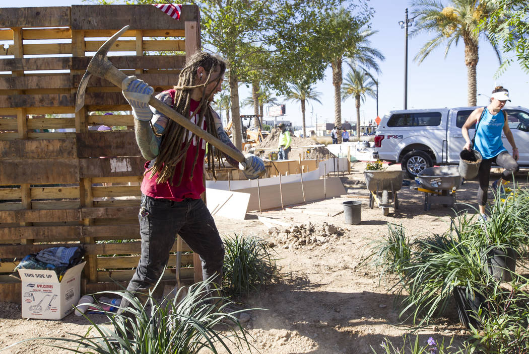 Las Vegas native Kelly Zurowski, 26, throws a pick as he volunteers at an under-construction community healing garden located at South Casino Center and East Charleston boulevards in downtown Las  ...