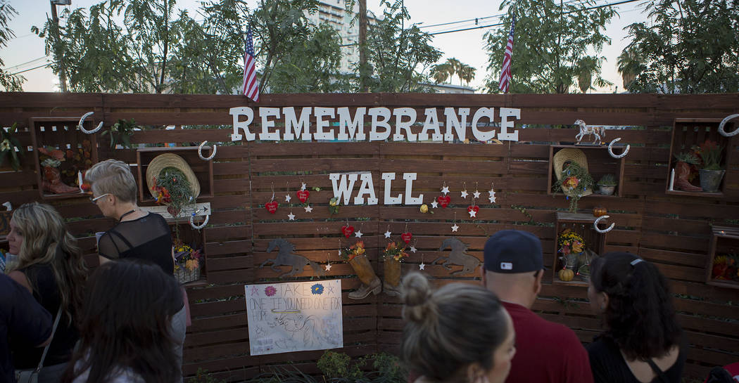 """Attendees walk past the """"Remembrance Wall"""" at the Community Healing Garden in Las Vegas, Friday, Oct. 6, 2017. The city of Las Vegas dedicated the new healing garden to victims o ..."""