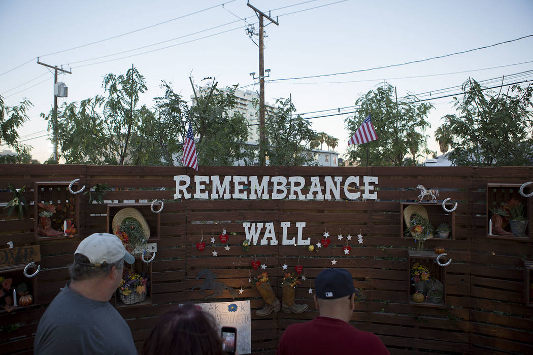 "Attendees walk past the ""Remembrance Wall"" at the Community Healing Garden in Las Vegas, Friday, Oct. 6, 2017. The city of Las Vegas dedicated the new healing garden to victims o ..."