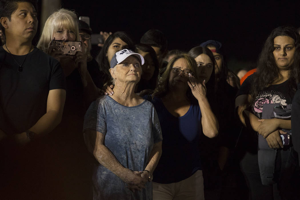 A woman wipes her eye while people speak about city of Las Vegas employee and Saturday shooting victim Cameron Robinson at the Community Healing Garden in Las Vegas, Friday, Oct. 6, 2017. The city ...