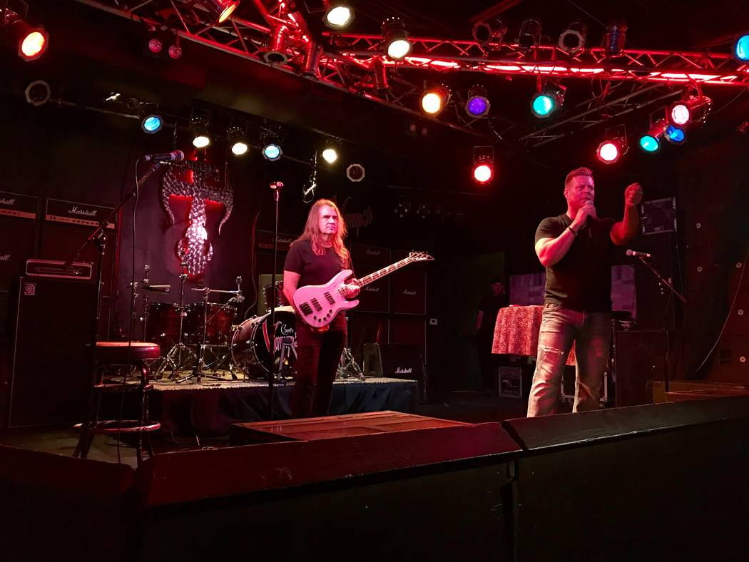 David Ellefson, poses with a signed bass guitar up for auction while Jeff Manning looks for bidders. An event at Count's Vamp'd Rock Bar & Grill on Oct. 5 raised over $3,000 for The Firefighte ...