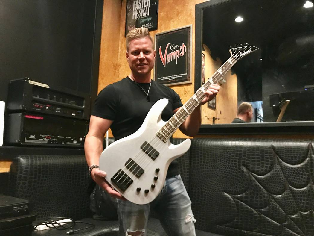 Auctioneer Jeff Manning poses with a bass guitar donated by Megadeth bassist David Ellefson. (Madelyn Reese/View) @MadelynGReese