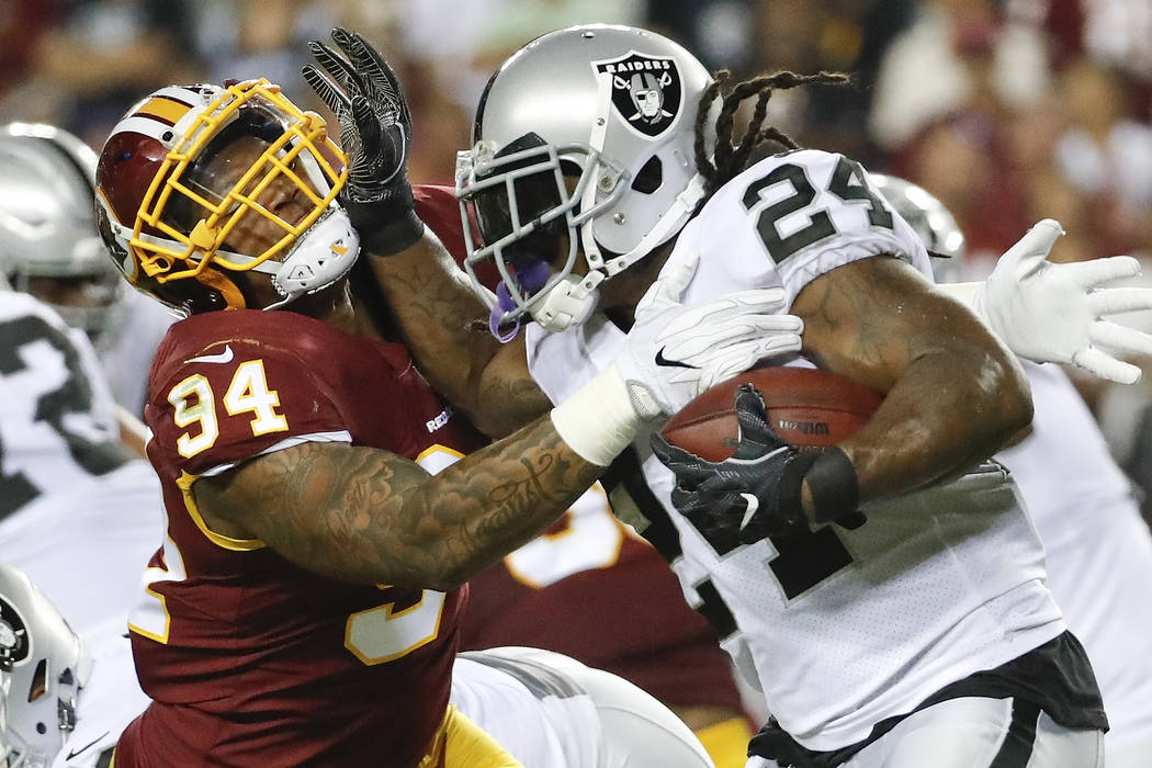 Oakland Raiders running back Marshawn Lynch (24) collides with Washington Redskins outside linebacker Preston Smith (94) during the first half of an NFL football game in Landover, Md., Sunday, Sep ...