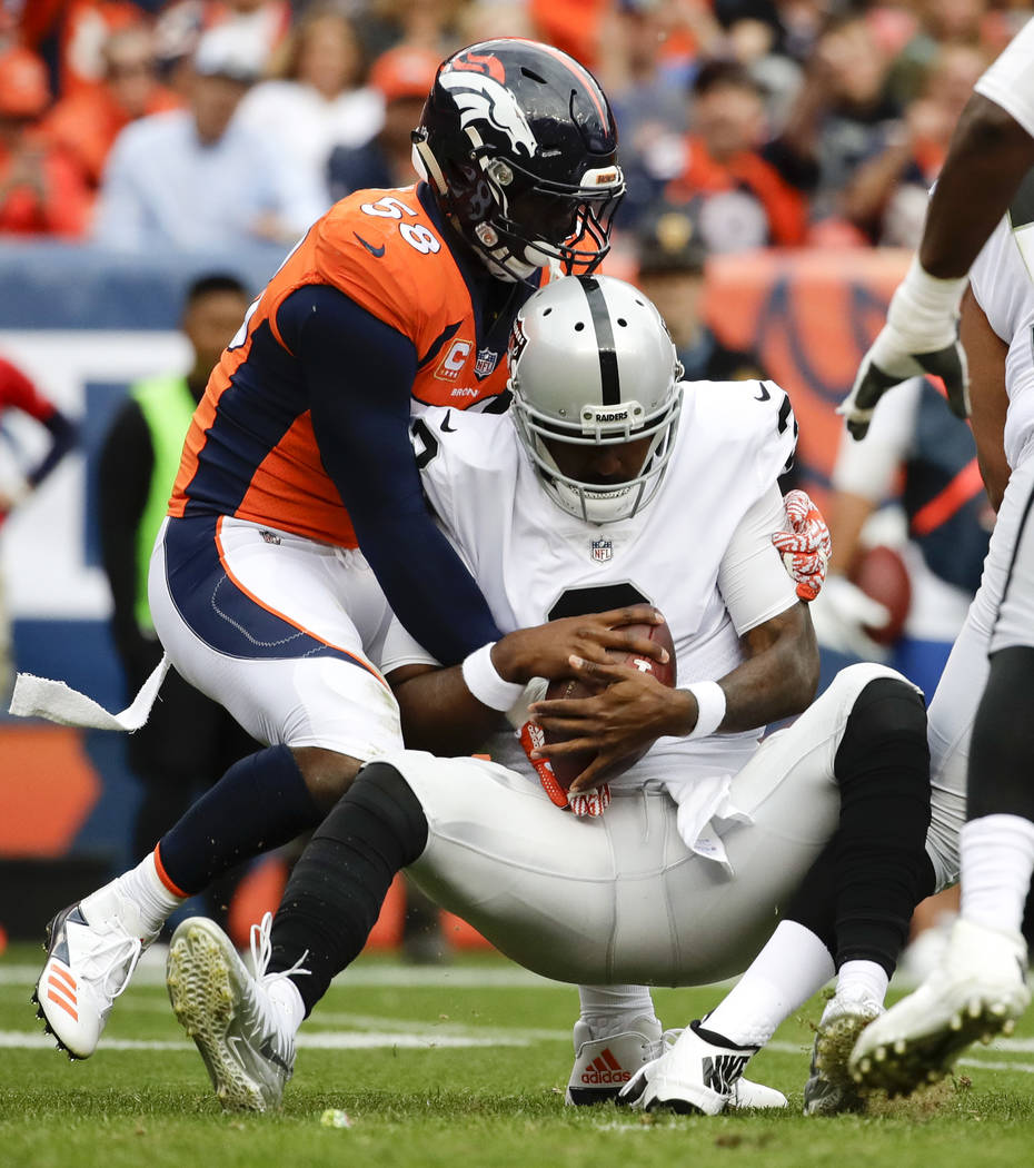 Denver Broncos outside linebacker Von Miller, left, sacks Oakland Raiders quarterback EJ Manuel during the second half of an NFL football game Sunday, Oct. 1, 2017, in Denver. (AP Photo/Jack Dempsey)