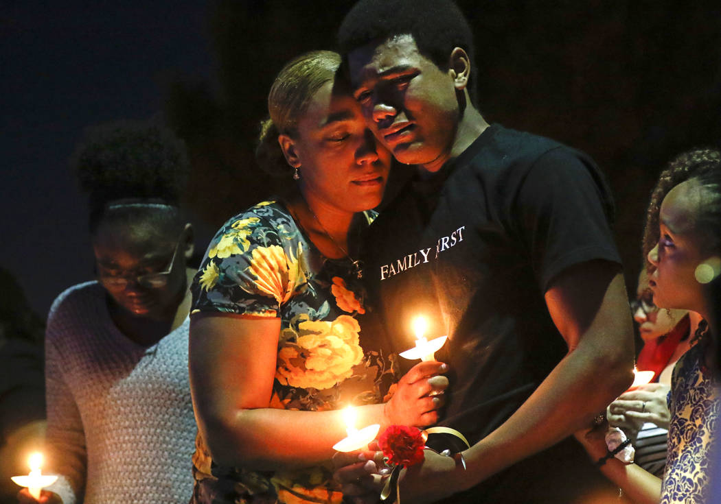 Veronica Hartfield, left, and son Ayzayah, wife and son of fallen officer Charleston Hartfield, during a candlelight vigil for in his memory at Police Memorial Park in Las Vegas on Thursday, Oct.  ...