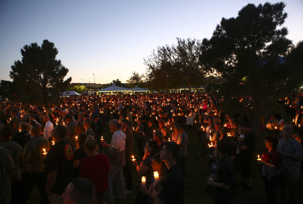 Attendees during a candlelight vigil for Las Vegas police officer Charleston Hartfield, who was killed while off-duty in Sunday's mass shooting, at Police Memorial Park in Las Vegas on Thursday, O ...