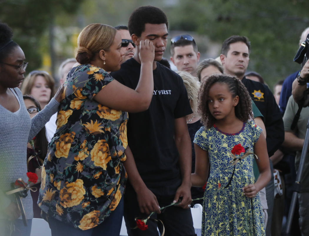 Veronica Hartfield, left, wipes tears from the eyes of her son Ayzayah, as daughter Savannah looks on during a candlelight vigil in memory of Las Vegas police officer Charleston Hartfield at Polic ...