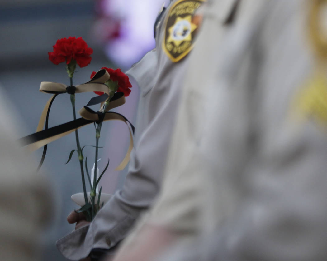 Las Vegas police officers hold roses during a candlelight vigil for Las Vegas police officer Charleston Hartfield, who was killed while off-duty in Sunday's mass shooting, at Police Memorial Park  ...