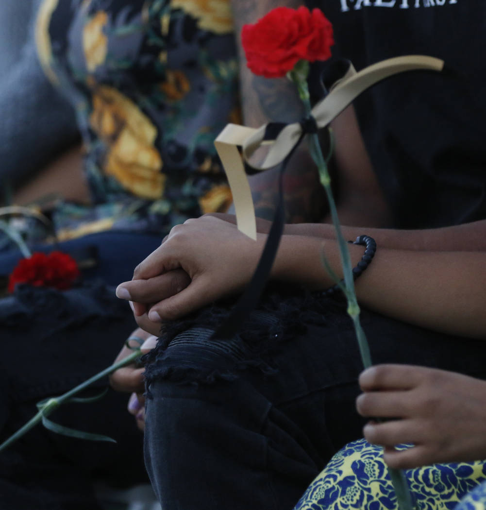 Ayzayah and Savannah Hartfield, children of fallen Las Vegas police officer Charleston Hartfield, hold hands during a candlelight vigil in Hartfield's memory at Police Memorial Park in Las Vegas o ...
