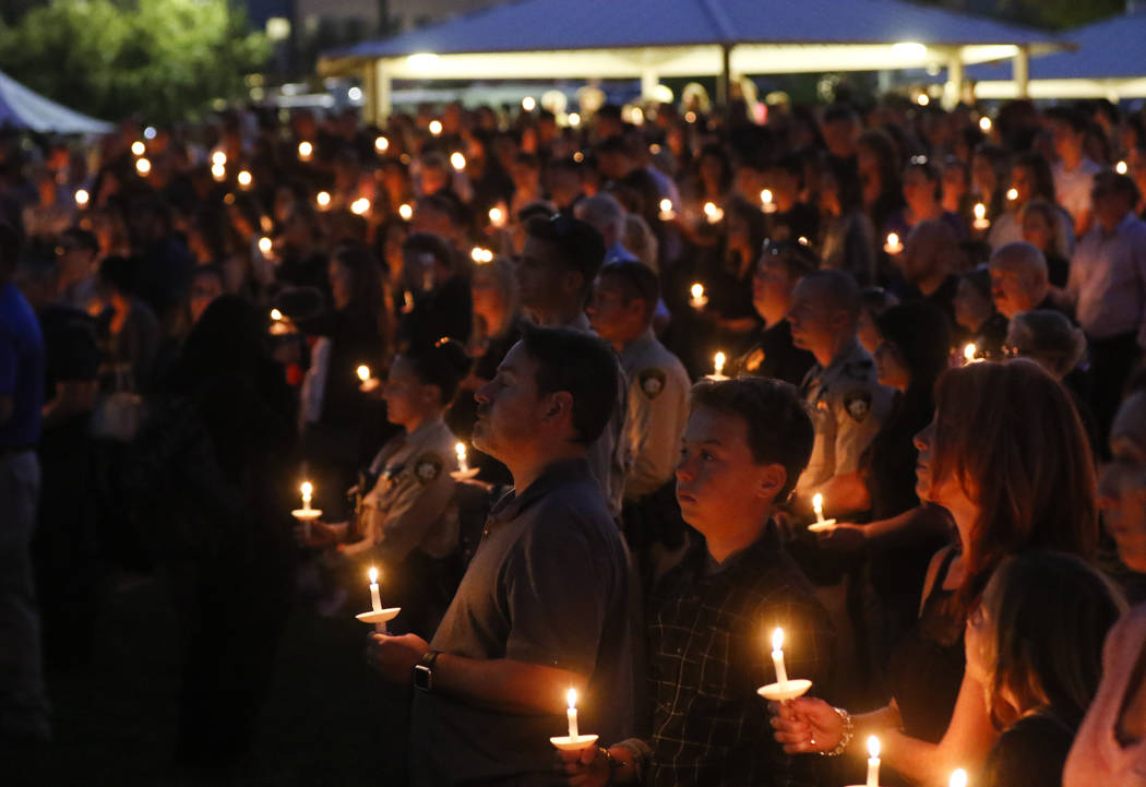 People attend a candlelight vigil for Las Vegas police officer Charleston Hartfield, who was killed while off-duty in Sunday's mass shooting, at Police Memorial Park in Las Vegas on Thursday, Oct. ...