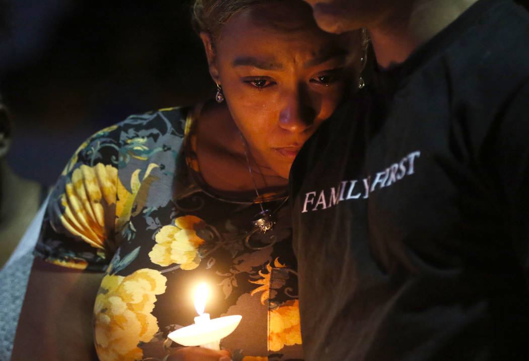 Veronica Hartfield, left, and Ayzayah, wife and son of fallen officer Charleston Hartfield, during a candlelight vigil for in his memory at Police Memorial Park in Las Vegas on Thursday, Oct. 5, 2 ...
