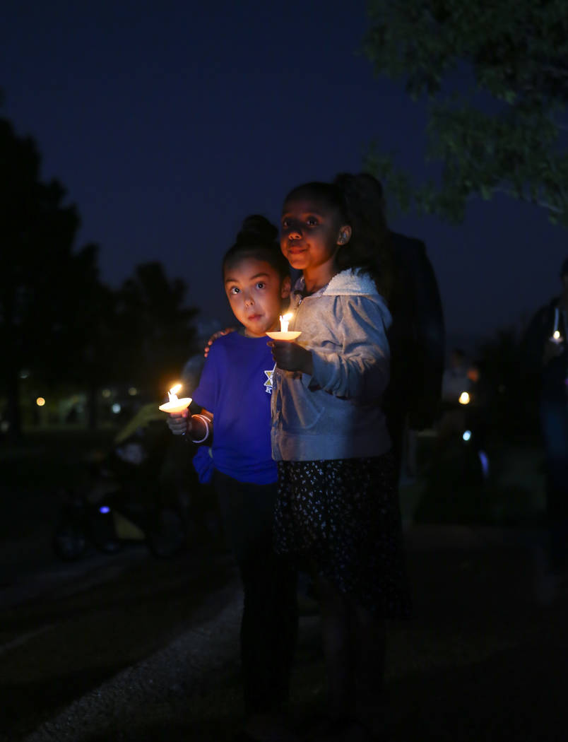 Seven-year-olds Abigail, left, and Naomee during a candlelight vigil for Las Vegas police officer Charleston Hartfield, who was killed while off-duty in Sunday's mass shooting, at Police Memorial  ...