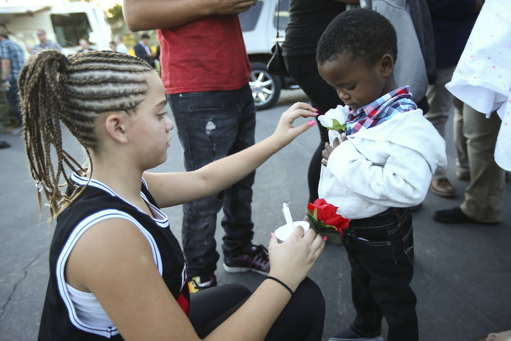 Twelve-year-old Mariah Bailor, a cousin of fallen Las Vegas police officer Charleston Hartfield, who was killed while off-duty in Sunday's mass shooting, puts a rose on Samajay Louis, 3, during a  ...