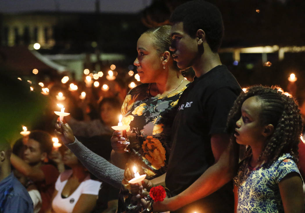 Veronica Hartfield, from left, with children Ayzayah, and Savanna,h family of fallen officer Charleston Hartfield, during a candlelight vigil for in his memory at Police Memorial Park in Las Vegas ...