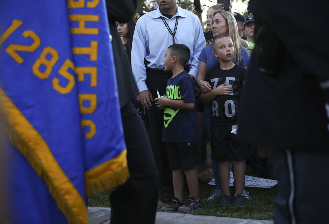 Attendees watch as the Honor Guard passes by during a candlelight vigil for Las Vegas police officer Charleston Hartfield, who was killed while off-duty in Sunday's mass shooting, at Police Memori ...