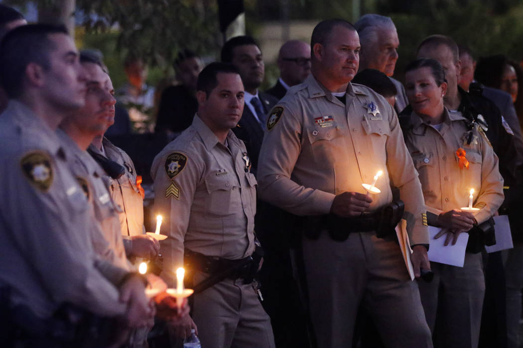 Las Vegas police officers during a candlelight vigil for Las Vegas police officer Charleston Hartfield, who was killed while off-duty in Sunday's mass shooting, at Police Memorial Park in Las Vega ...