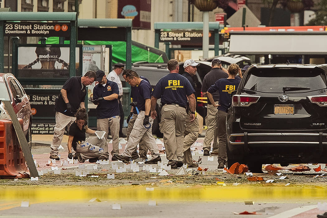 In this Sunday, Sept. 18, 2016 file photo, members of the Federal Bureau of Investigation (FBI) carry on investigations at the scene of an explosion on West 23rd Street and Sixth Avenue in Manhatt ...