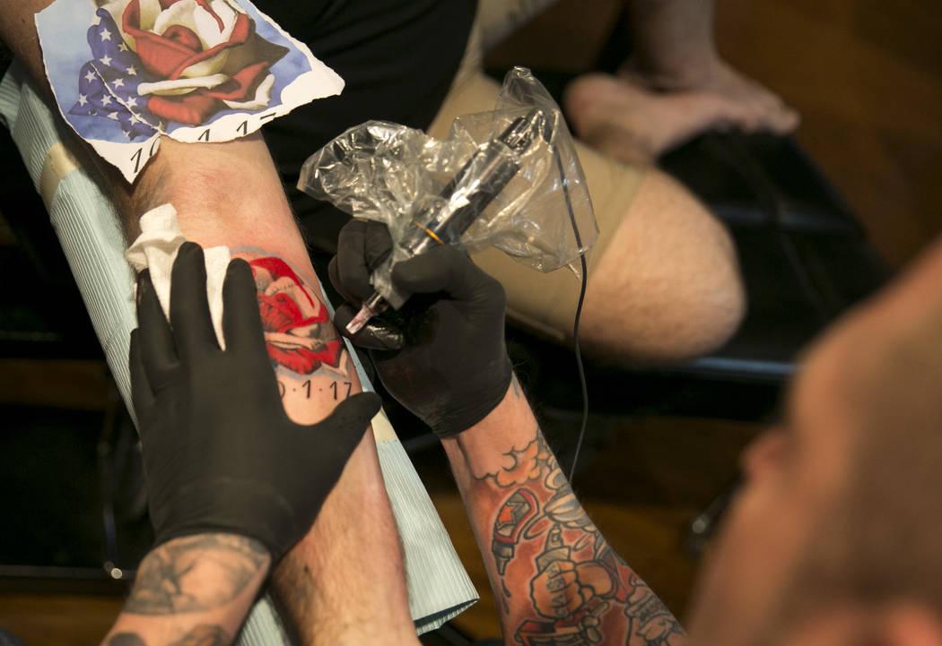 Brett Davis, left, of Australia gets a Route 91 Harvest  memorial tattoo from artist Justin Vanbibber at Club Tattoo inside Planet Hollywood, Thursday, Oct. 5, 2017, in Las Vegas. Richard Brian La ...